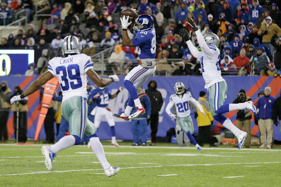 New York Giants wide receiver Victor Cruz (80) completes a pass in front of Dallas Cowboys' J.J. Wilcox (27) during the second half of an NFL football game, Sunday, Nov. 24, 2013, in East Rutherford, N.J. (AP Photo/Seth Wenig) Photo: Seth Wenig, Associated Press / AP