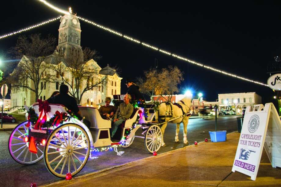 Horse-drawn carriages take visitors to candlelit homes during Granbury's historic home tour. Photo: Courtesy Photo, Granbury CVB