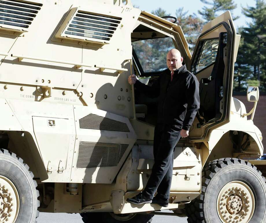 Warren County Undersheriff Shawn Lamouree poses on the department's  mine resistant ambush protected vehicle, or MRAP, on Wednesday, Nov. 13, 2013, in Queensbury, N.Y. The hulking vehicles, built for about $500,000 each at the height of the war, are among the biggest pieces of equipment that the Defense Department is giving to law enforcement agencies under a national military surplus program. (AP Photo/Mike Groll) ORG XMIT: NYMG203 ORG XMIT: MER2013112508013103 Photo: Mike Groll / AP