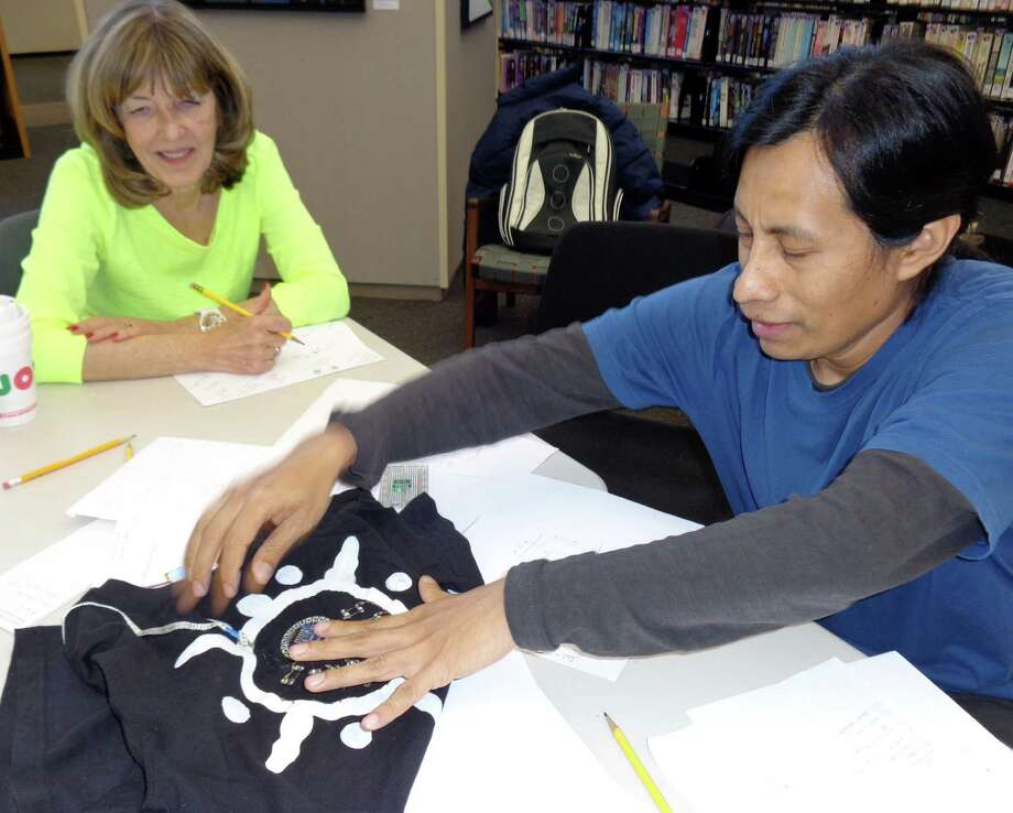 Westport Library's Maker-in-Residence, Balam Soto, shows Karen Gustafson how the digital quilt project will work by showing her a tee-shirt he made that incorporates tecnological elements into the hand-painted design. Photo: Meg Barone / Westport News contributed
