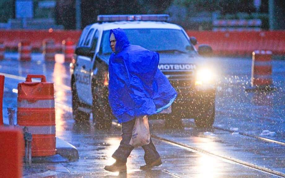 A pedestrian endures the cold and rain Monday, Nov. 25, 2013, as he walks along Bagby Street in downtown Houston. Photo: Cody Duty, Houston Chronicle