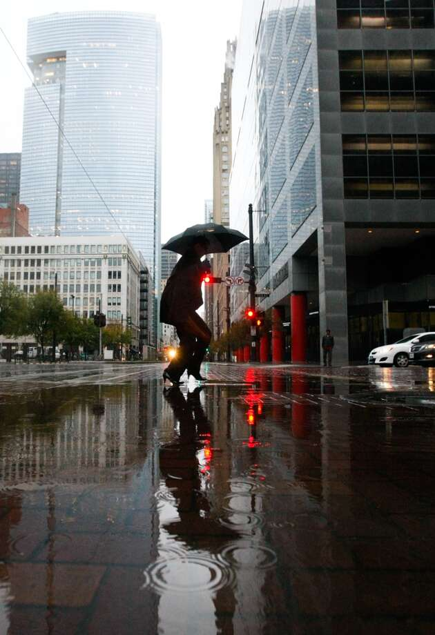 Leesa Everitt crosses a puddle early Monday morning along Texas Avenue in downtown Houston. Photo: Cody Duty, Houston Chronicle