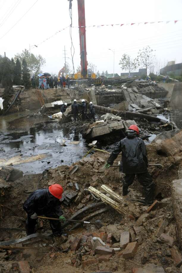 Workers dig through rubble at the site of a pipeline explosion in Qingdao Development Zone, in Qingdao, east China's Shandong Province, Sunday, Nov. 24, 2013 Photo: Li Ziheng, ASSOCIATED PRESS