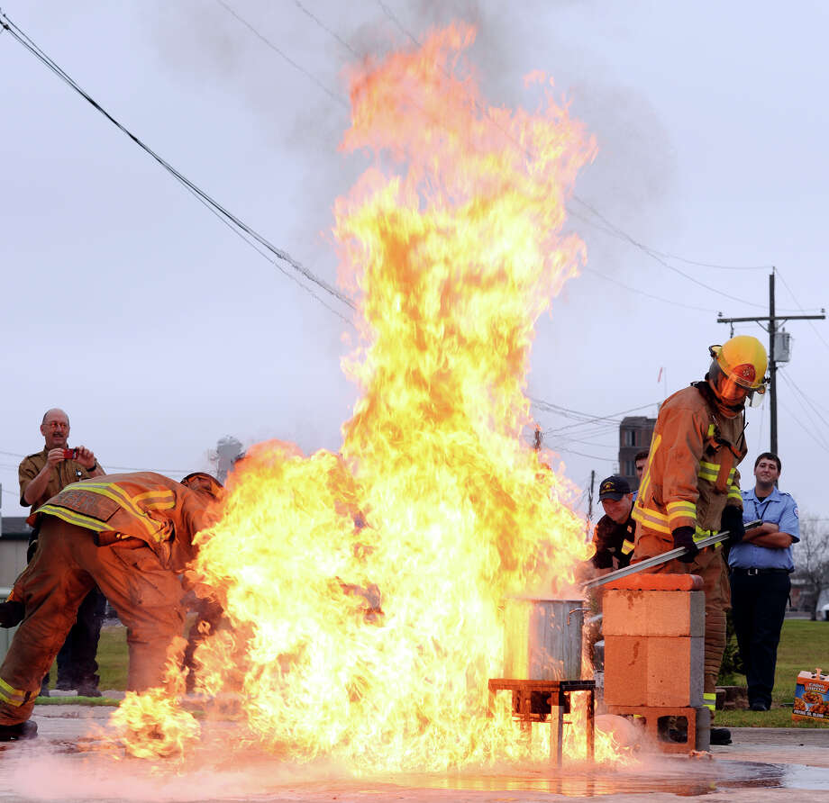 Fireman Matt Kiser, left, steps in to turn off the propane tank while Andy Brown drops a frozen turkey into an overfilled pot of oil as it spills over and catches fire Friday morning. The Beaumont Fire Department demonstrated the dangers of improperly frying a turkey at their training facility Friday morning. Texas is ranked number one in the nation for turkey frying incidents. Photo taken Jake Daniels/@JakeD_in_SETX Photo: Jake Daniels / ©2013 The Beaumont Enterprise/Jake Daniels