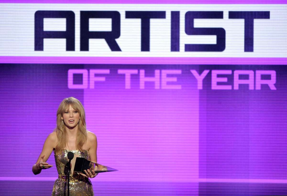 Taylor Swift accepts the award for artist of the year at the American Music Awards at the Nokia Theatre L.A. Live on Sunday, Nov. 24, 2013, in Los Angeles. (Photo by John Shearer/Invision/AP) ORG XMIT: CACJ466