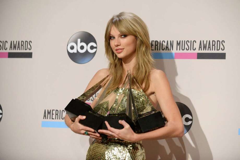 "Taylor Swift poses backstage with the awards for favorite album - country for ""Red"", favorite female artist - pop/rock, favorite female artist - country, and artist of the year at the American Music Awards at the Nokia Theatre L.A. Live on Sunday, Nov. 24, 2013, in Los Angeles. (Photo by Jordan Strauss/Invision/AP) ORG XMIT: CACJ390 Photo: Jordan Strauss, AP / Invision"