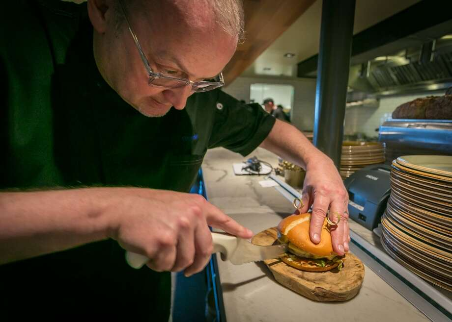 her Bruce Hill cuts the Fog City Burger at Fog City in San Francisco. Photo: John Storey, Special To The Chronicle