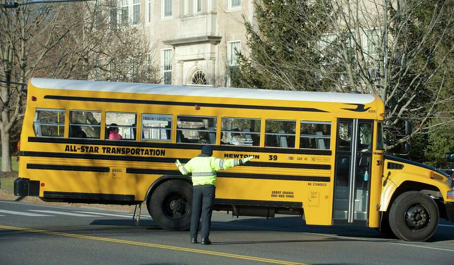 A school bus is directed into the driveway of the Hawley School in Newtown, Conn.  Police officers were at the Newtown school as part of the school's security. A report on the Sandy Hook shootings is scheduled to be released today by State's Attorney Stephen Sedensky. It is expected to be a summary of the full state police report on the, December 14, 2012, Newtown, Conn, shooting, on Monday November 25, 2013. Photo: H John Voorhees III / The News-Times Freelance