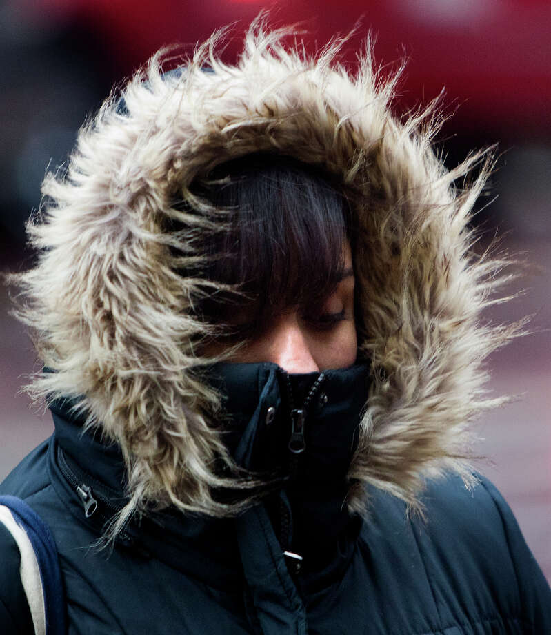 Rosia Hernandez bundles up as she walks along Main Street, Monday, Nov. 25, 2013, in Houston. The forecast calls for one hundred percent chance of rain and a high of 45 degrees. Photo: Cody Duty, Houston Chronicle / © 2013 Houston Chronicle