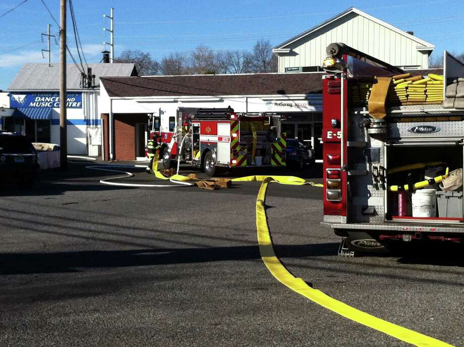 Firefighters at the scene where fire was reported in the shopping center at 1580 Post Road on Monday afternoon. Photo: Genevieve Reilly / Fairfield Citizen