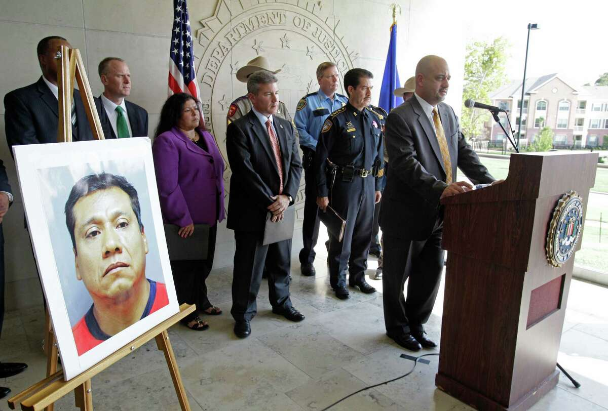 """A photo of fugitive Alfonso Diaz-Juarez, aka """"Poncho""""is displayed as Houston FBI Special Agent in Charge Stephen L. Morris, right, speaks during media conference at FBI Houston Headquarters, 1 Justice Park Drive, Friday, Oct. 11, 2013, in Houston. The multi-agency media conference was held to announce multiple federal arrests, and to seek public assistance in the ongoing investigation of an international sex-trafficking ring in which 14 have been charged. Twelve victims were recovered including five minors. ( Melissa Phillip / Houston Chronicle )"""
