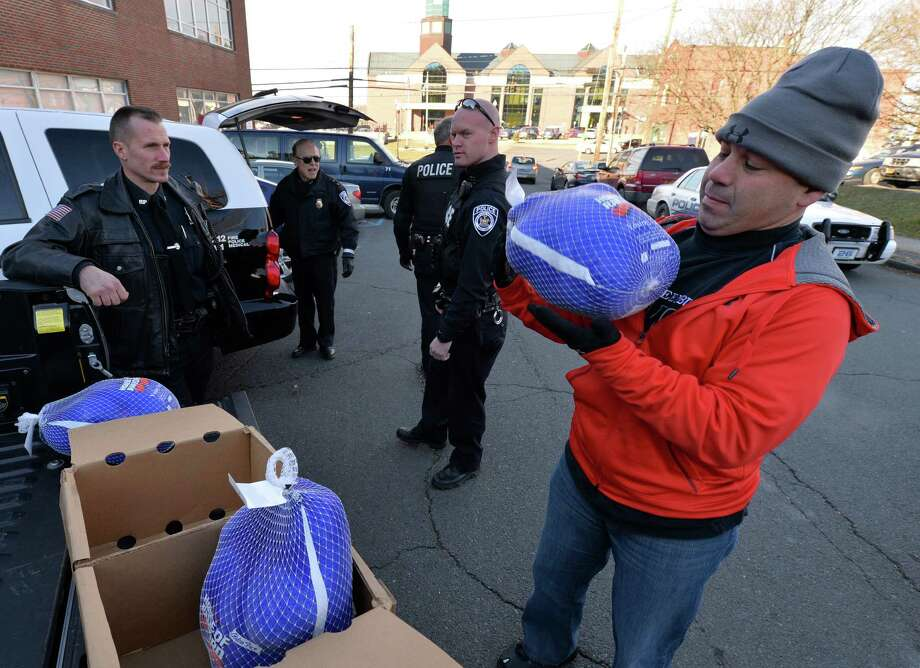 East Greenbush police Sgt. Ernest Tubbs, right, is joined by other members of the department Monday morning Nov. 25, 2013, in delivering turkeys, potatoes and pies to the Concerns U charity in Rensselaer, N.Y.  Members of the East Greenbush PBA purchased 25 turkeys, 25 pounds of potatoes and pies and made the donation.      (Skip Dickstein/Times Union) Photo: SKIP DICKSTEIN / 00024750A