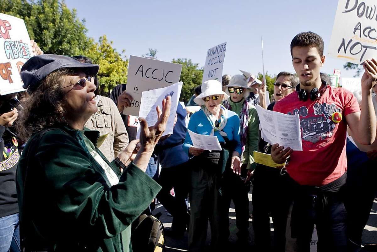 Pat Wynne leads protestors in a song at the Accrediting Commission for Community and Junior Colleges headquarters in Novato, Ca, on Friday, Oct. 11, 2013.