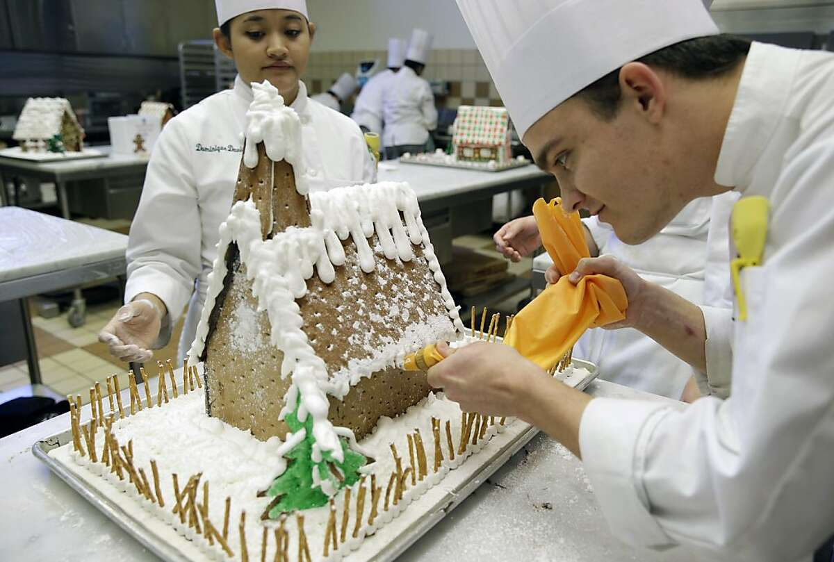 Home, sweet home: Student chef Chris Mitchell puts the finishing touches on his gingerbread house at the Culinary Institute of America in St. Helena, Calif. A group of students were making the houses for display in the windows of local stores for the holidays.