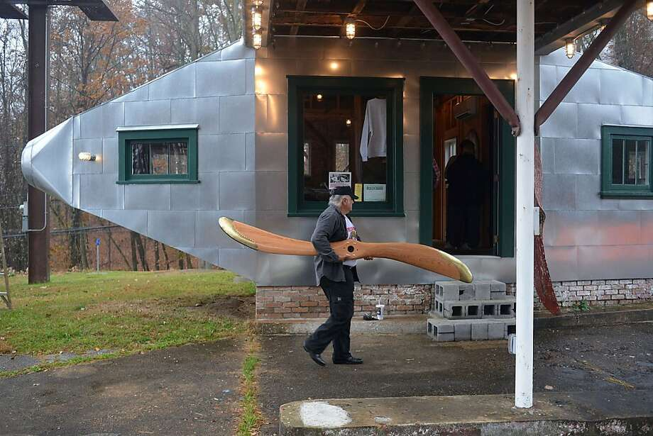 "Now she'll fly!	Tom Bruno carries a donated propeller into the ""fuselage"" of the Airplane Filling Station 