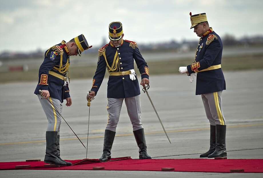 Maybe they should have fumigated it first: As Romania rolls out the red carpet for China's premier at Bucharest's Henri Coanda airport, an honor guard draws swords to dispatch any critters that might have been living inside. Photo: Vadim Ghirda, Associated Press