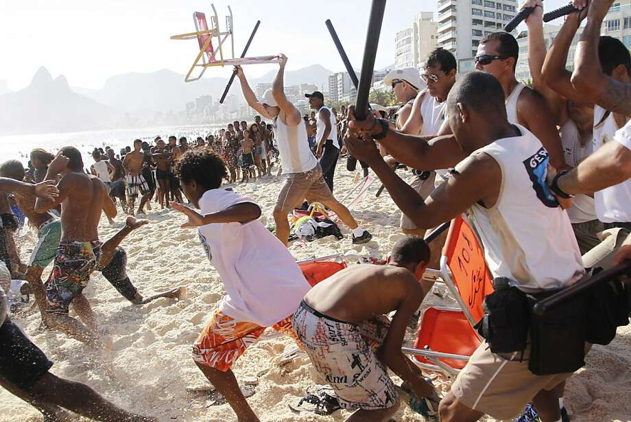 Club-wielding municipal guards chase a gang of thieves on Arpoador Beach in Rio de Janeiro last week. Photo: Marcelo Carnaval, Associated Press