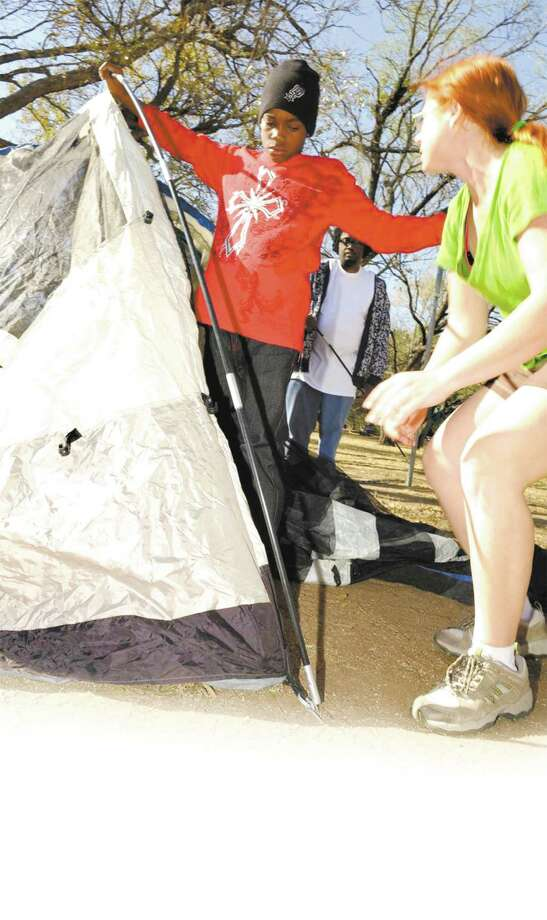 A young participant at a Texas Outdoor Family workshop practices assembling a tent. Photo: Photos Courtesy Texas Parks And Wildlife