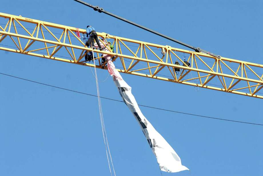 Protestors outside 66 Summer Street in Stamford, Conn. have climbed a crane and unfurled a banner protesting UBS and its mountaintop mining practices on Monday November 25, 2013. Photo: Dru Nadler / Stamford Advocate Freelance