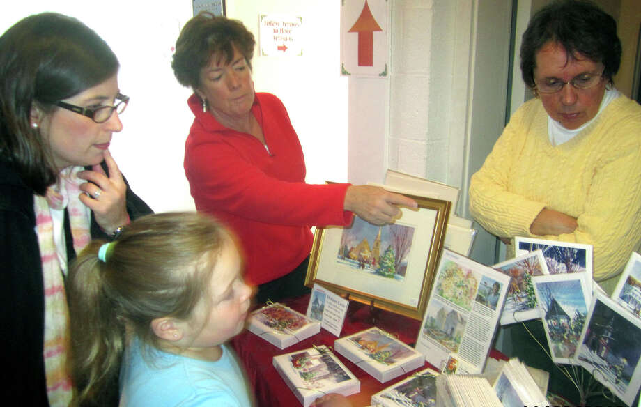 New Milford artist Diane Dubreuil points out a particular holiday card among those she created for sale during the New Milford Historical Society & Museum's annual Christmas shop and artisan show, Nov. 22-23, 2013. Patron Ilona Pomeroy and her daughter, Gabrielle, 7, of New Milford peruse the possibliities as historial society volunteer Pat Lathrope, right, looks on. Photo: Norm Cummings / The News-Times