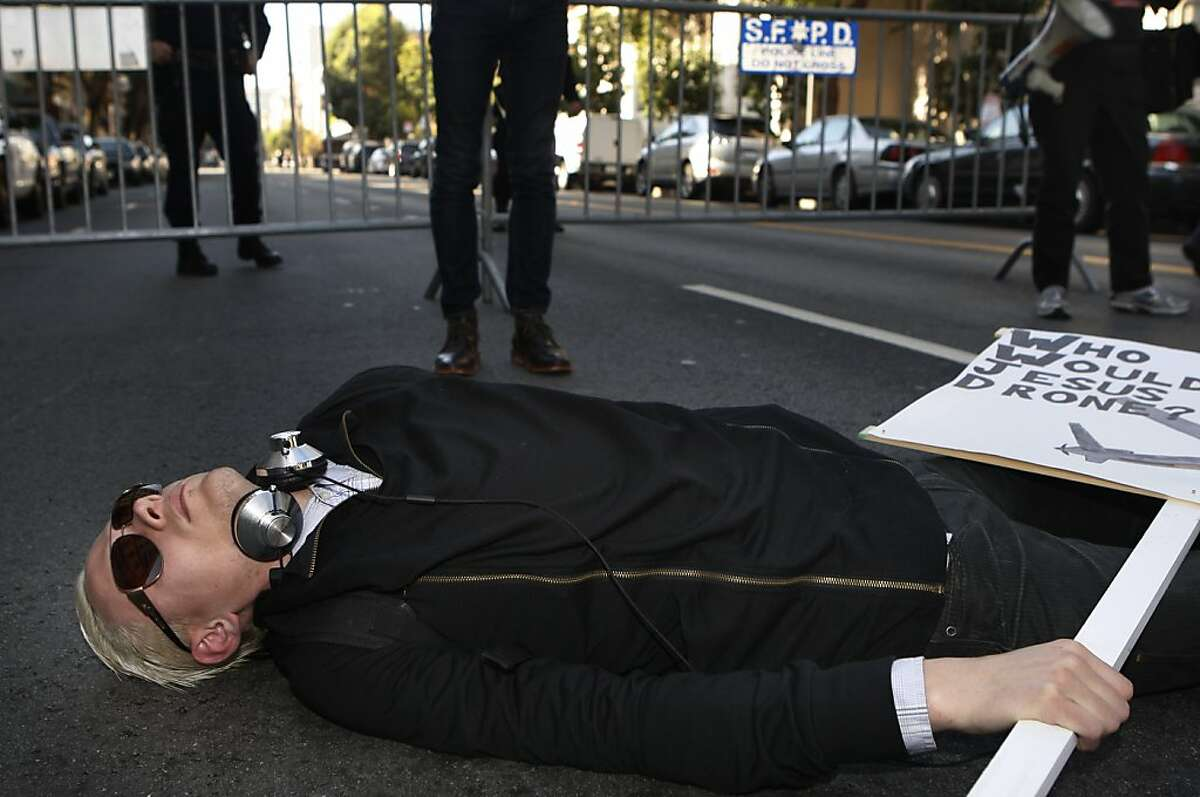 Sam, a member of Iraq Veterans Against War lays on the street during President Barack Obama's luncheon fundraiser at the SF Jazz Center in San Francisco, Calif., on Monday, November 25, 2013. Protesters say that Obama's drone policy is responsible for the deaths of hundreds of innocent civilians in Pakistan and Yemen.