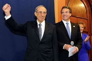 Former Gov. Mario Cuomo, left, pumps his fist as the crowd cheers before his portrait is revealed in the Hall of Governors on Saturday, June 15, 2013, at the Capitol in Albany, N.Y. Joining him are his son, Gov. Andrew Cuomo, center, and the former First Lady Matilda Cuomo. (Cindy Schultz / Times Union)
