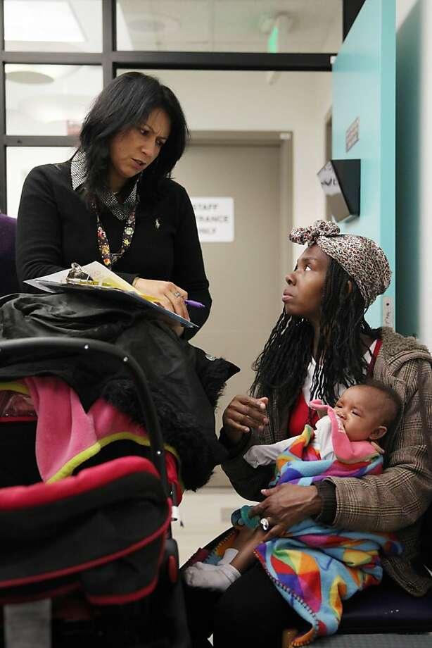 "LaTanya Ross holds Taraji Warrick as she meets with family ""navigator"" Yolanda Pulido-Lopez. Photo: Lea Suzuki, The Chronicle"
