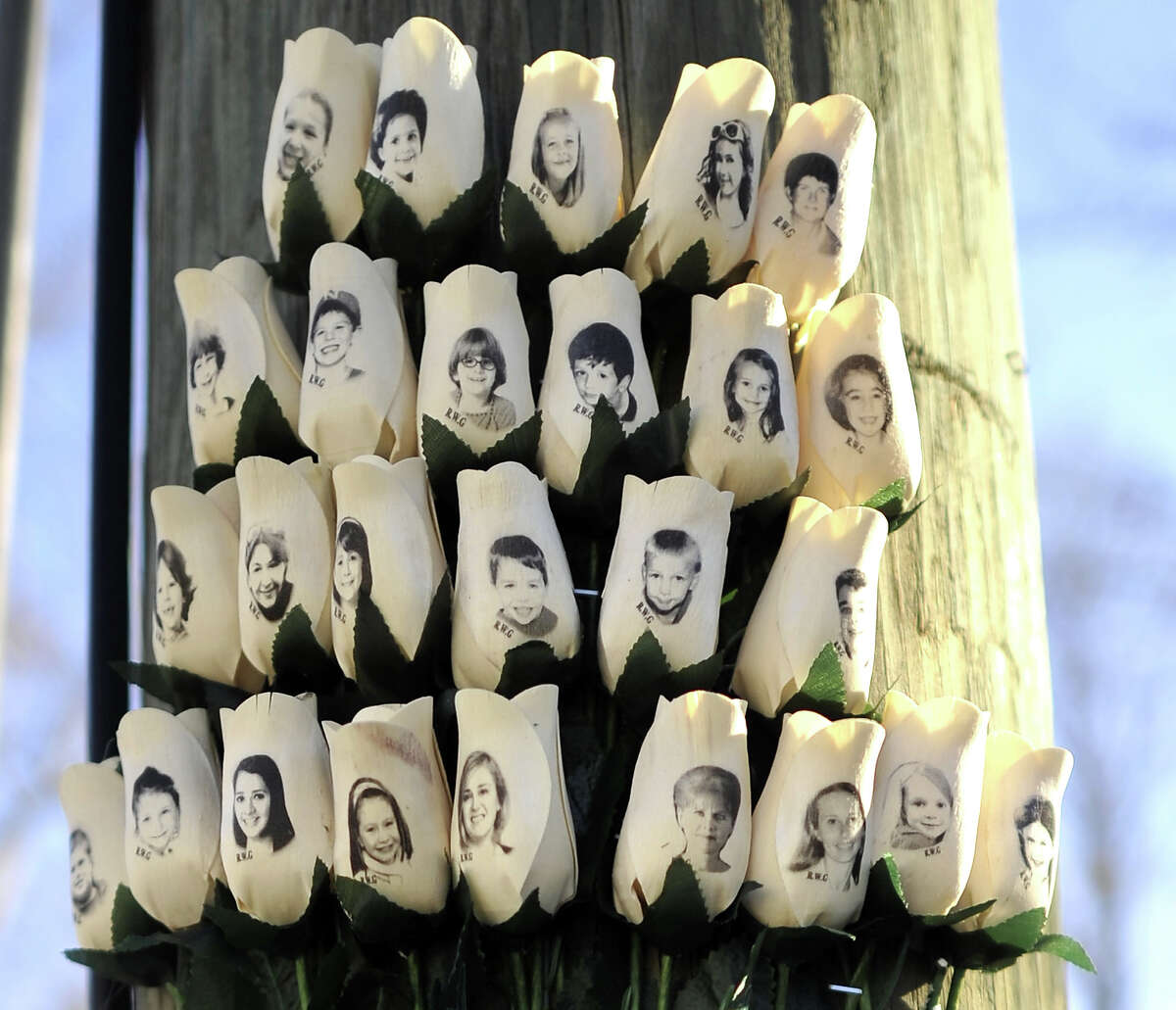 Roses with the faces of the Sandy Hook Elementary students and adults killed are seen on a pole in Newtown, Connecticut on January 3, 2013.