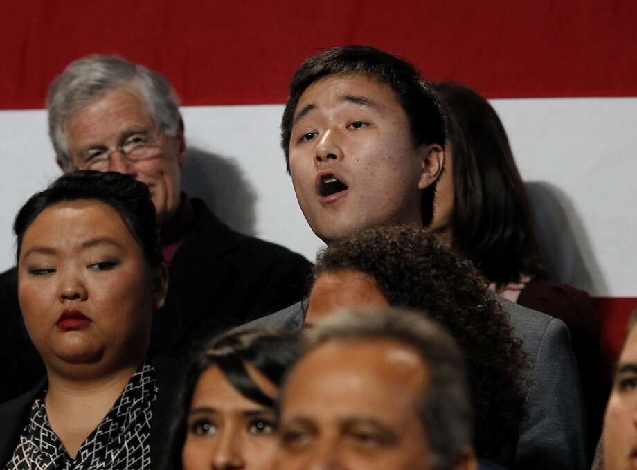 Protester Ju Hong, 24,  in the crowd in back of the President, yelled at him to help his family. President Obama spoke at the Betty Ong Recreation Center, on the outskirts of Chinatown, about passing immigration reform Monday November 25, 2013. Photo: The Chronicle