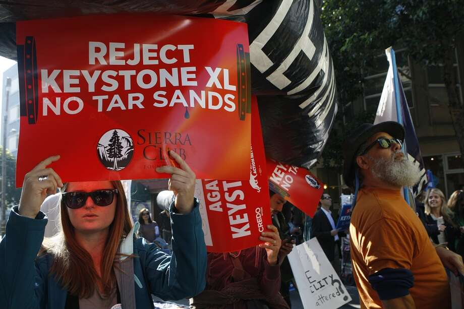 Protestor Jessica Ronald from the Sierra club protests the Keystone XL pipeline on Franklin Street during President Barack Obama's luncheon fundraiser at the SF Jazz Center in San Francisco, Calif., on Monday, November 25, 2013. Photo: Chronicle