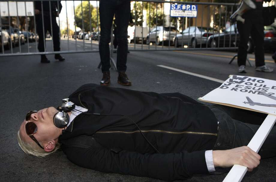 Sam, a member of  Iraq Veterans Against War lays on the street during President Barack Obama's luncheon fundraiser at the SF Jazz Center in San Francisco, Calif., on Monday, November 25, 2013.  Protesters say that Obama's drone policy is responsible for the deaths of hundreds of innocent civilians in Pakistan and Yemen. Photo: Chronicle