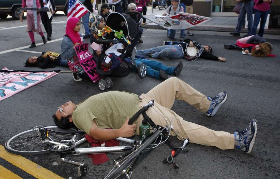 Code pink protestors lay on the street during President Barack Obama's luncheon fundraiser at the SF Jazz Center in San Francisco, Calif., on Monday, November 25, 2013.  Protesters say that Obama's drone policy is responsible for the deaths of hundreds of innocent civilians in Pakistan and Yemen. Photo: Chronicle