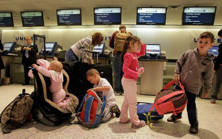 Marilynne and Justin Zborowski, of The Woodlands, check in Monday at Bush Intercontinental with their daughters and nephews. The family will be spending Thanksgiving at grandmother's house in Arizona. Photo: Melissa Phillip, Staff / © 2013  Houston Chronicle