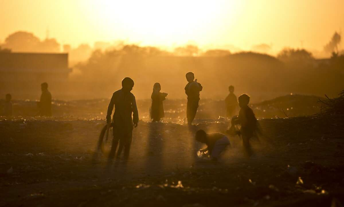 Afghan refugee children play in a field as the sun sets on the outskirts of Islamabad, Pakistan, Monday, Nov. 25, 2013. Pakistan hosts over 1.6 million registered Afghans, the largest and most protracted refugee population in the world, according to the U.N. refugee agency, with thousands living without electricity, running water and other basic services.