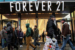 In this Dec. 26, 2010 file photo, people walk past a Forever 21 store in New York's Times Square. The population of the U.S. has grown by 8 million people since the previous record was set. That means there were millions more shoppers in stores this Christmas, driving up the sales total. But the average amount of spending per person was down from a few years ago, suggesting consumers are still slower to pull out their wallets. (AP Photo/Mary Altaffer, file)