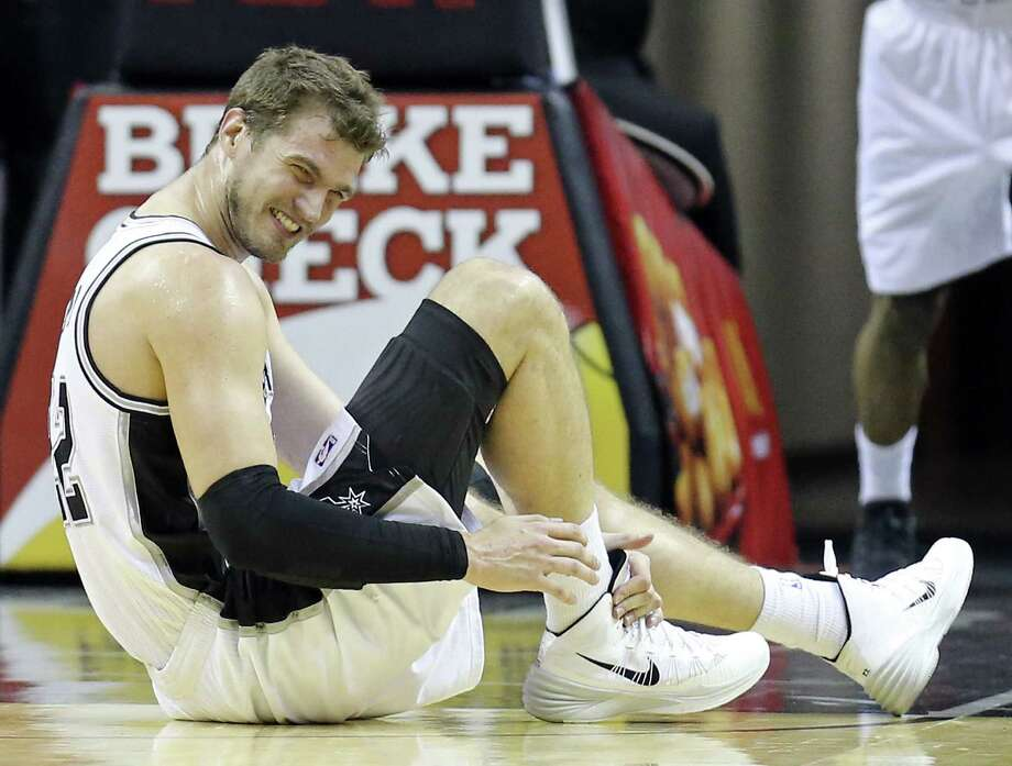 The Spurs' Tiago Splitter holds his right ankle after spraining it early in the second quarter Monday. Photo: Edward A. Ornelas / San Antonio Express-News