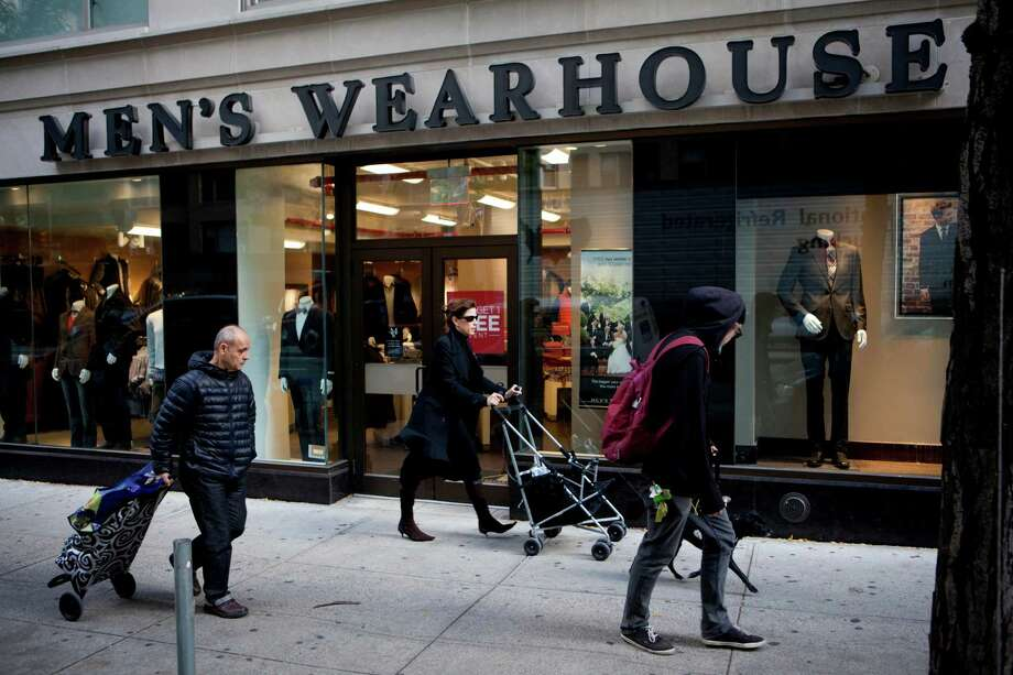 Pedestrians pass in front of a Men's Wearhouse Inc. store in New York, U.S., on Thursday, Oct. 24, 2013. Men's Wearhouse Inc., the suit retailer that rejected a $2.3 billion offer from Jos. A. Bank Clothiers Inc., may bid for Allen Edmonds Corp., a closely held shoemaker, according to a person familiar with the matter. Photographer: Mati Milstein/Bloomberg Photo: Mati Milstein / © 2013 Bloomberg Finance LP