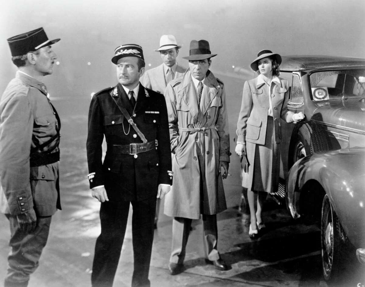 """""""Casablanca"""" sequel: Ilsa gets on the plane alright, but tells her husband everything and declares her love for Rick. Then hearing Rick's warning that she would regret it if she stayed - """"Maybe not today, maybe not tomorrow, but soon and for the rest of your life"""" - she is overcome with a jealous rage, takes over the plane and crashes it into the fog ... magically missing Rick ... the two set out Cat and Mouse fashion across the war torn world. Photo: A movie still of (L-R) Unidentified, Claude Rains, Paul Henreid, Humphrey Bogart and Ingrid Bergman on the set of the Warner Bros classic film 'Casablanca' in 1942 in Los Angeles, California."""