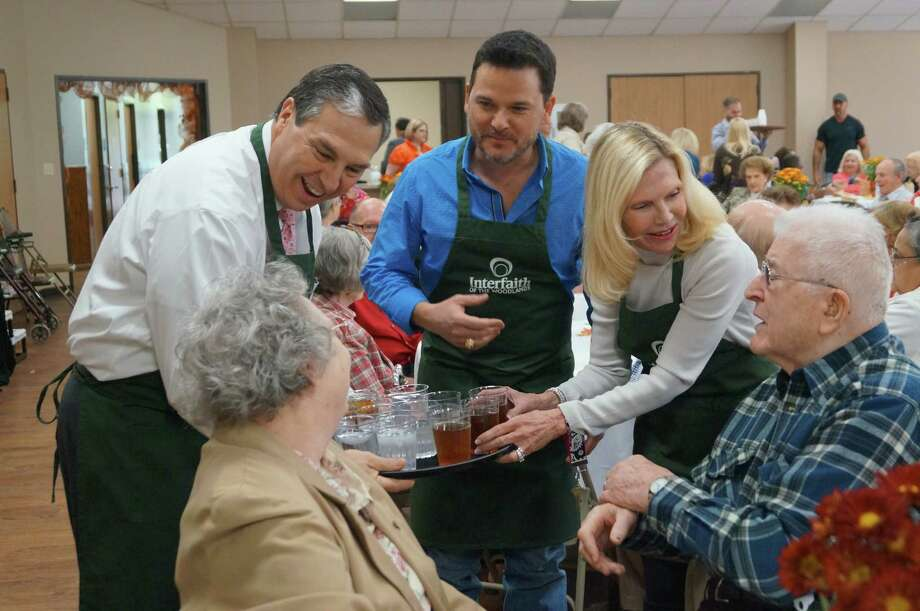 Interfaith board member Ray Sanders joins Precinct 3 Commissioner James Noack and Ann Snyder, president and CEO of Interfaith of The Woodlands, in serving a Thanksgiving feast to seniors at the South County Community Center. Photo: Interfaith Of The Woodlands Photo