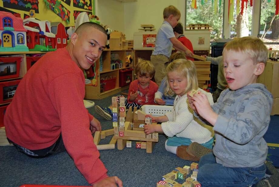 Luis Sanchez, Molly Kilroy and John Miller spend some quality time together when Darien High School students visited the Methodist Family Center Preschool. Photo: Contributed Photo, Contributed / Darien News