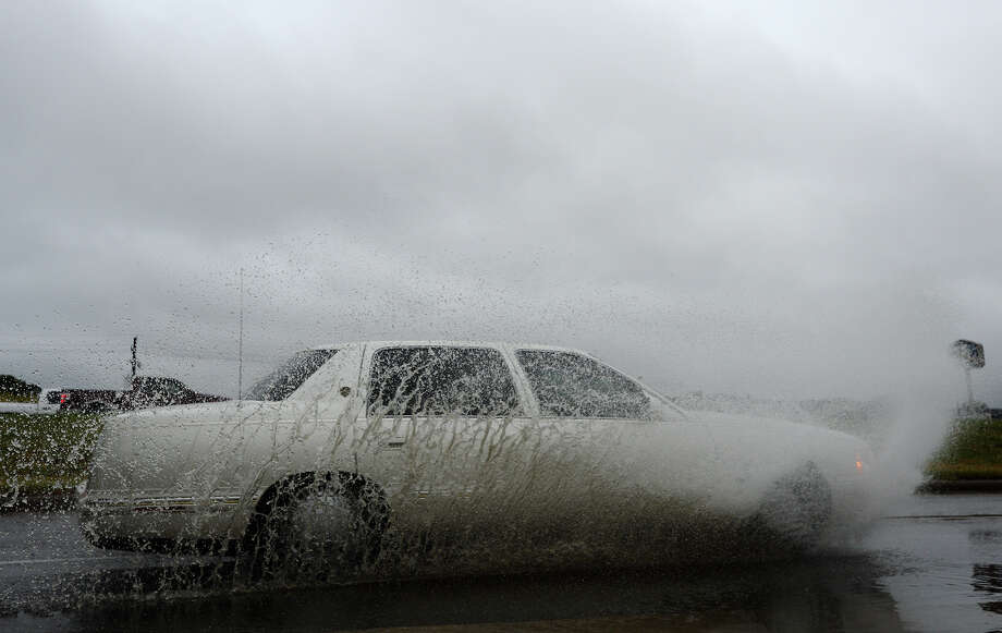 A car splashes through a puddle on the I-10 service road during wet weather Monday afternoon. Holiday travelers will be contending with cold, wet weather in addition to traffic this Thanksgiving, as a large cold front is forecast to move through the region over the course of the week. Photo taken Jake Daniels/@JakeD_in_SETX Photo: Jake Daniels / ©2013 The Beaumont Enterprise/Jake Daniels