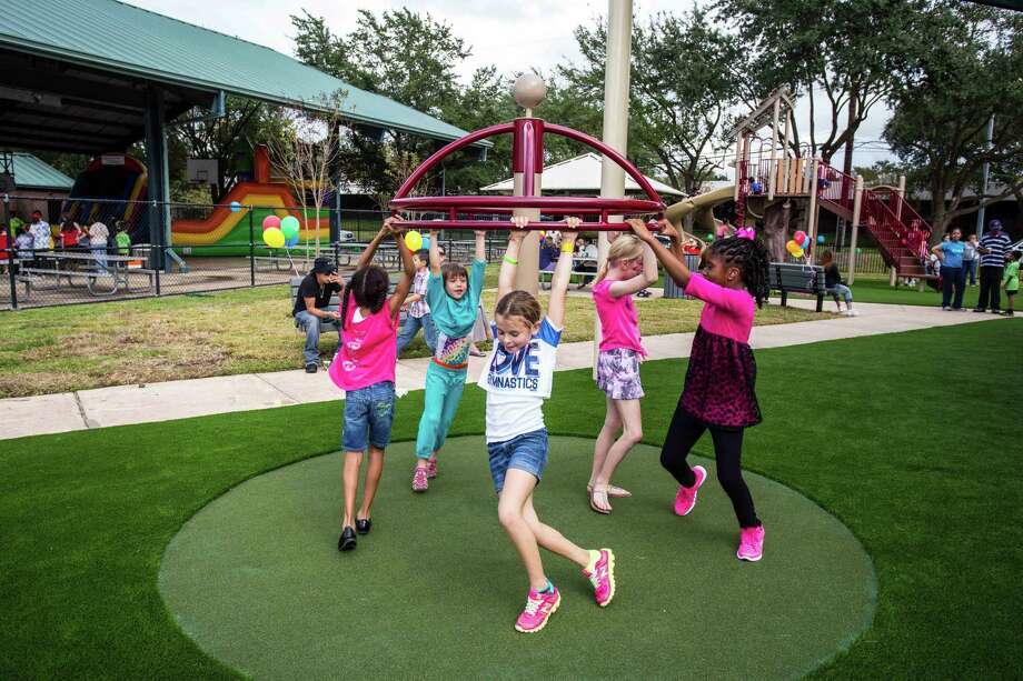 Children play at the grand opening of the Quillian Center's playground. Photo: Photo By Quillian Center