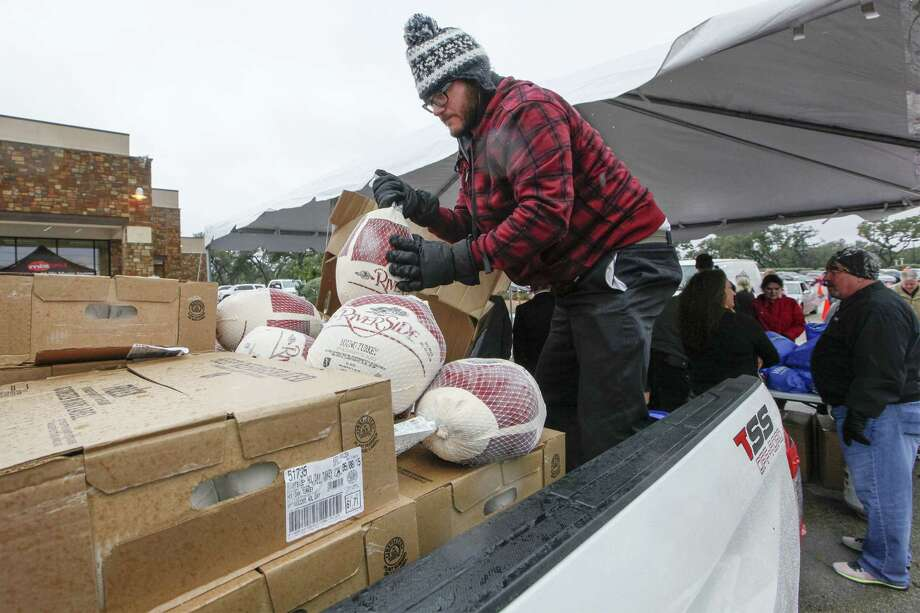"Volunteer Jonathan Garcia unloads frozen turkeys to be given to veterans and their families during Toyota of Boerne's ""Turkeys for Troops"" event Friday. Photo: Marvin Pfeiffer / Northwest Weekly"