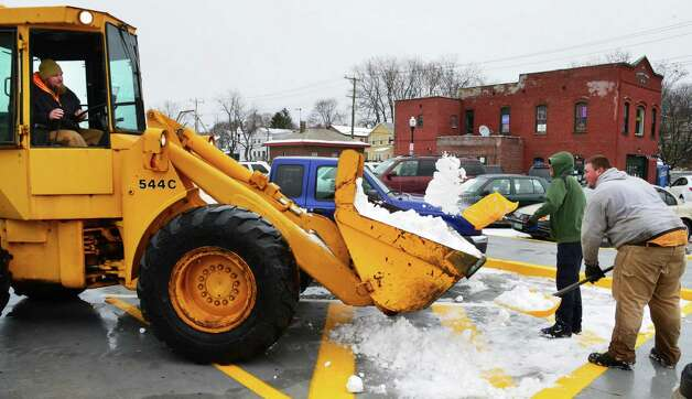 SMS Property Maintenance workers ,from left, JD Barnes, Mike Stoddard and Kyle Witco remove snow from the parking lot at the Rensselaer Train Station Tuesday Nov. 26, 2013, in Rensselaer, NY.  (John Carl D'Annibale / Times Union) Photo: John Carl D'Annibale / 00024809A