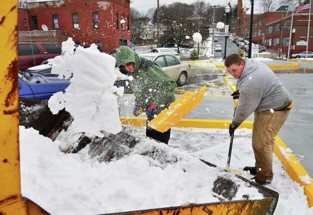 SMS Property Maintenance workers Mike Stoddard, left, and Kyle Witco load snow into a front end loader as they clear from the parking lot at the Rensselaer Train Station Tuesday Nov. 26, 2013, in Rensselaer, NY.  (John Carl D'Annibale / Times Union) Photo: John Carl D'Annibale / 00024809A