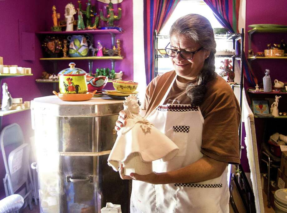 At the MujerArtes cooperative on the West Side, Patricia de la Garza shows one of her artworks pulled from the kiln. The gray clay turns white when it's fired in the kiln. Photo: Ricardo Segovia / For Conexion
