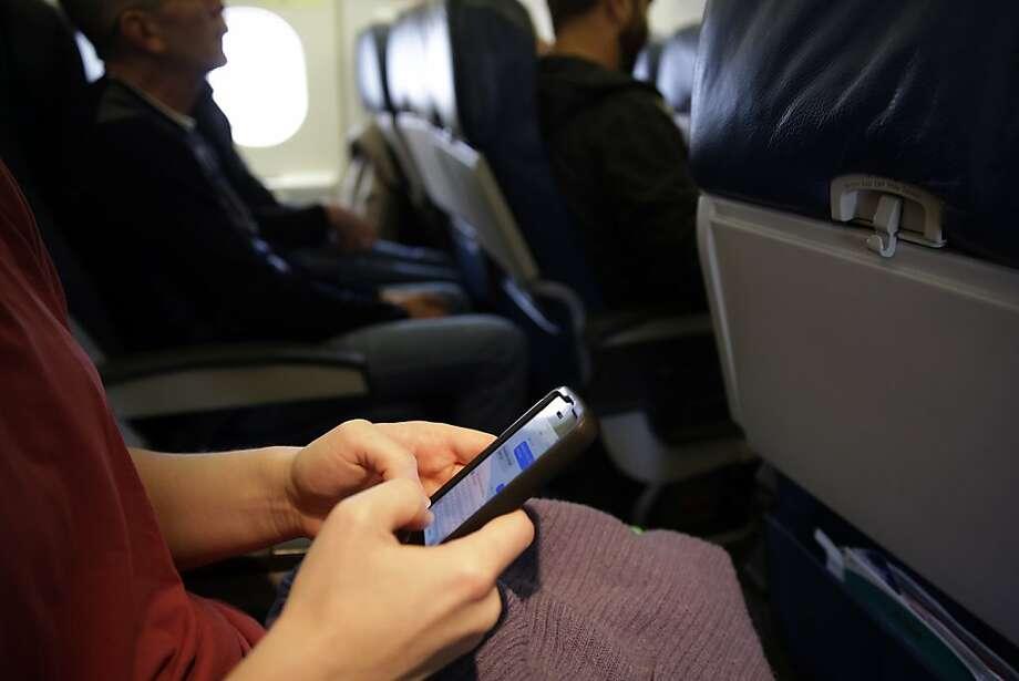 A passenger checks her cell phone before a flight in Boston. Photo: Matt Slocum, Associated Press