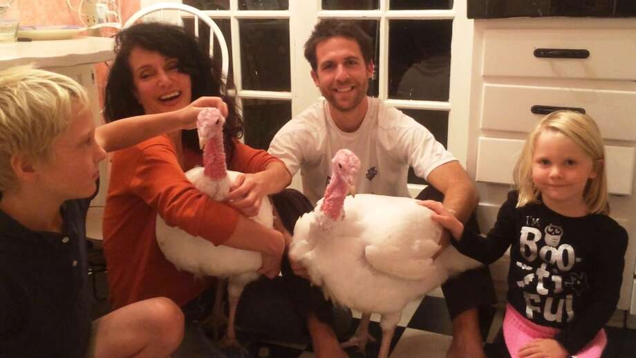 Neighbors Wade and Ruby Nieman pose with their new turkey friends. Photo: Ros Nieman, Courtesy Karen Dawn