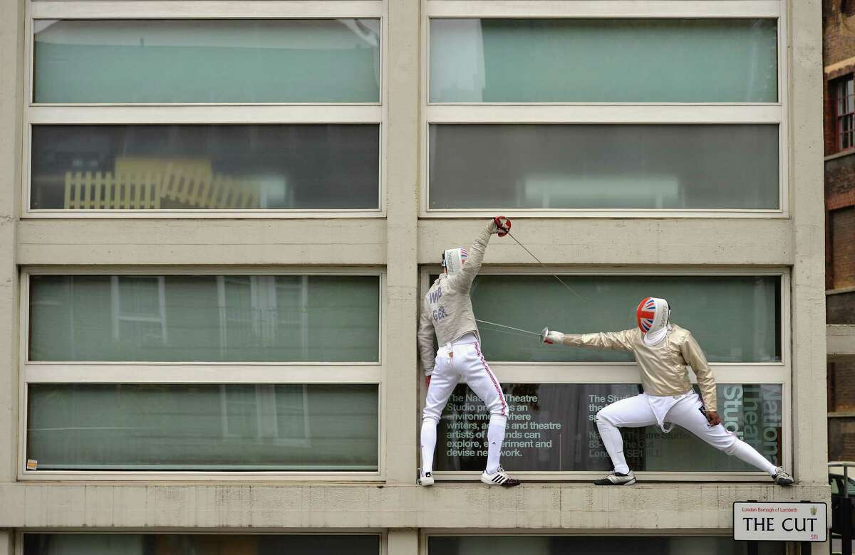 Fencing on the sides of buildings Jonathan Webb and Soji Aiyenuro British fencers taking part in a calendar photoshoot at fencing related street signs around London for their sponsor, specialist insurer Beazley on November 24, 2013 in London, England.