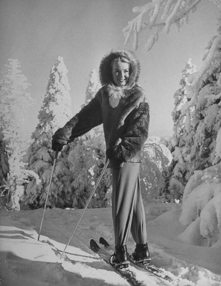 1944: Ski Fashions: Model wearing deerhide jacket with raccoon-edged hood, fur-lined mittens and trim pants on slopes at Mont Tremblant. Photo: Alfred Eisenstaedt, Time & Life Pictures/Getty Image
